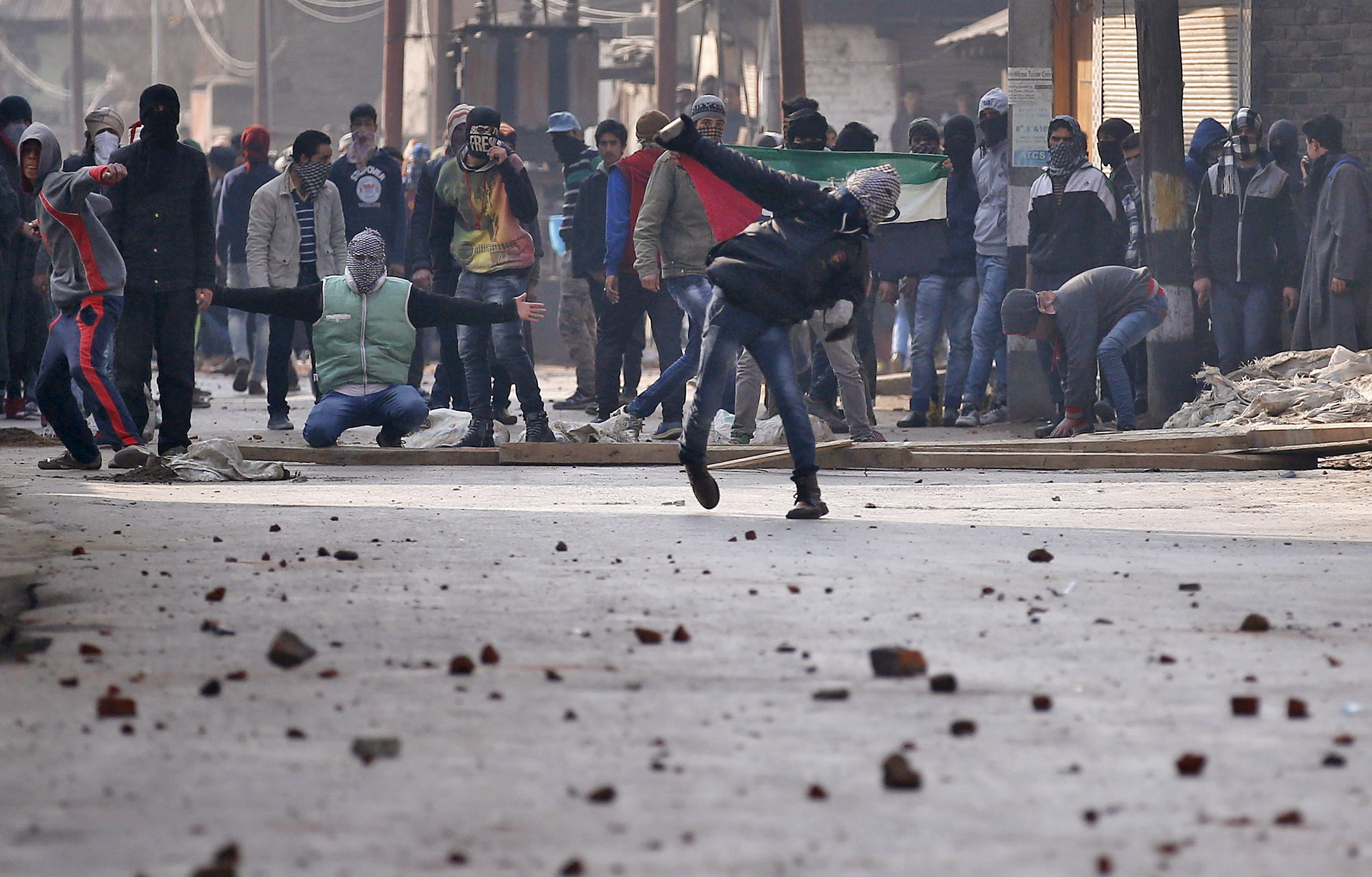 A Kashmiri protester throws a stone towards Indian police during a protest in Srinagar, January 15, 2016. The protesters demonstrated after Friday prayers demanding what they said was freedom from Indian rule in Kashmir. REUTERS/Danish Ismail - RTX22ILB