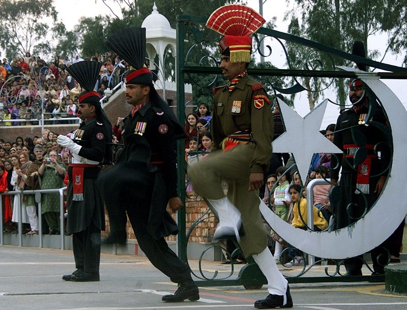 An Indian border security soldier (R) and Pakistani rangers (L) perform during a parade during a retreat ceremony at the Indo-Pak Joint check post in Wagha, December 30, 2004. Sector commanders of the Border Security Force (BSF) and Pakistani rangers met in the Wagha border town to share intelligence and exchange legal help against drug trafficking. REUTERS/Munish Sharma SD/CN - RTRJ8ZB