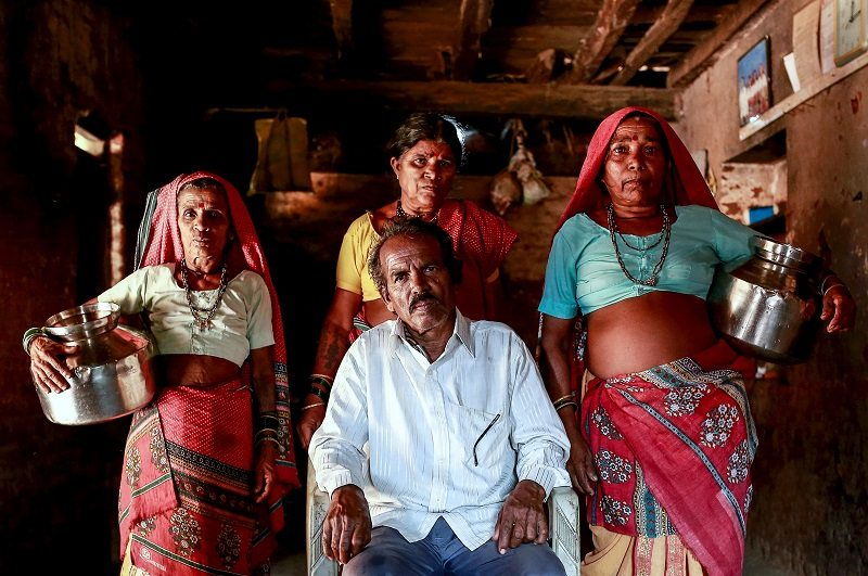 "Sakharam Bhagat, 66, poses with his wives, Sakhri, Tuki and Bhaagi (L to R) inside their house in Denganmal village, Maharashtra, India, April 20, 2015. In Denganmal, a village in Maharashtra state, some men take a second or third wife just to make sure their households have enough drinking water. Becoming what are known as ""water wives"" allows the women, often widows or single mothers, to regain respect in conservative rural India by carrying water from the well quite some distance from the remote village. When the water wife, who does not usually share the marital bed, becomes too old to continue, the husband sometimes takes a third and younger spouse to fetch the water in metal pitchers or makeshift containers. REUTERS/Danish Siddiqui PICTURE 8 OF 29 FOR WIDER IMAGE STORY ""WATER WIVES OF MAHARASHTRA""??SEARCH ""WATER WIVES"" FOR ALL IMAGES - RTX1F2OI"