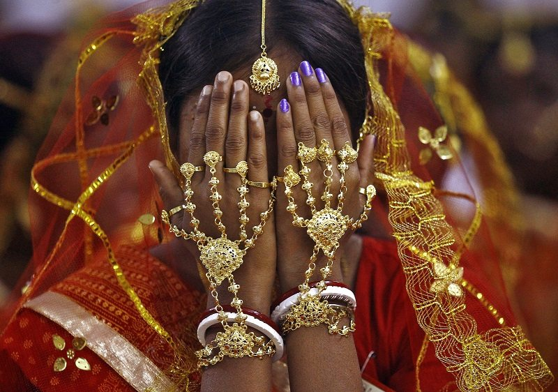 A bride covers her face as she waits to take her wedding vow at a mass marriage ceremony at Bahirkhand village, north of Kolkata February 8, 2015. A total of 108 tribal Muslim and Hindu couples from various villages across the state took their wedding vows on Sunday during the day-long mass marriage ceremony organised by a social organisation, the organisers said. REUTERS/Rupak De Chowdhuri (INDIA - Tags: SOCIETY) - RTR4OOJP