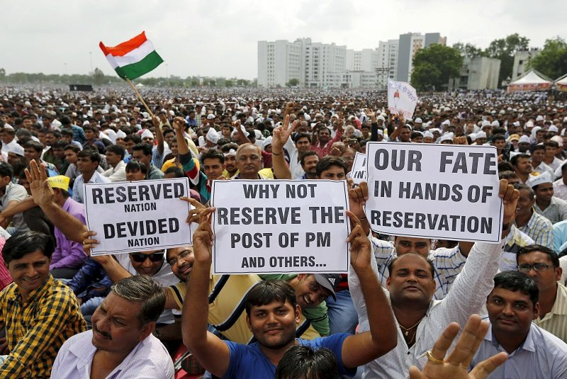 Members of the Patel community display placards as they attend a protest rally in Ahmedabad, India, August 25, 2015. Thousands of community members on Tuesday held the huge protest rally to demand reservation for their community, local media reported. REUTERS/Amit Dave - RTX1PJL6