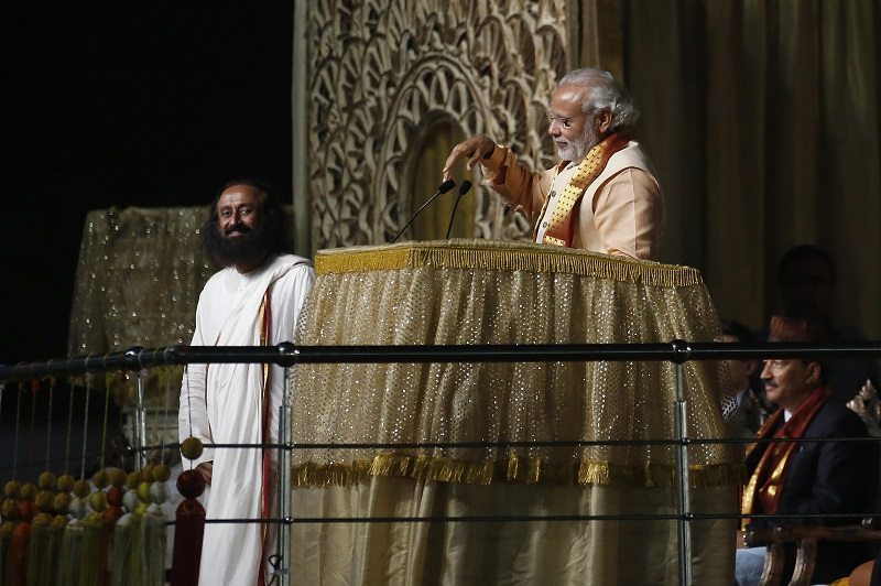 India's Prime Minister Narendra Modi addresses the gathering as Sri Sri Ravi Shankar (L), a well known guru, watches during World Culture Festival on the banks of the river in New Delhi, India, March 11, 2016. REUTERS/Adnan Abidi - RTSAE01
