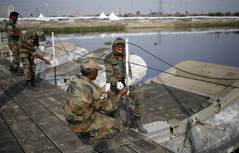 Army soldiers paint railings on a pontoon bridge laid in the waters of the Yamuna river to reach the venue of the World Culture Festival on the banks of the river in New Delhi, India, March 10, 2016. Indian environmentalists are aghast that a huge cultural festival is to be held on the floodplain of Delhi's main river from Friday, warning that the event, and the 3.5 million visitors expected, will devastate the area's biodiversity. REUTERS/Anindito Mukherjee - RTSA6GR