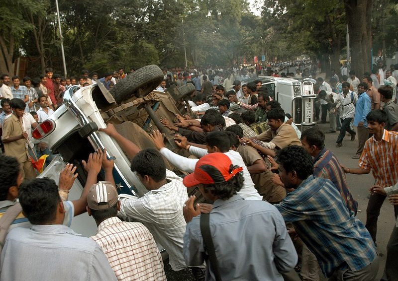 A mob of people overturns a police car after hearing news of the death of veteran Indian film actor Rajkumar in the southern Indian city Bangalore April 12, 2006. An icon of south Indian cinema and star of more than 200 films, Rajkumar, died on Wednesday, sparking widespread violence as distraught fans torched buses and ripped up hoardings in the country's hi-tech hub. REUTERS/Jagadeesh Nv - RTR1CGDJ