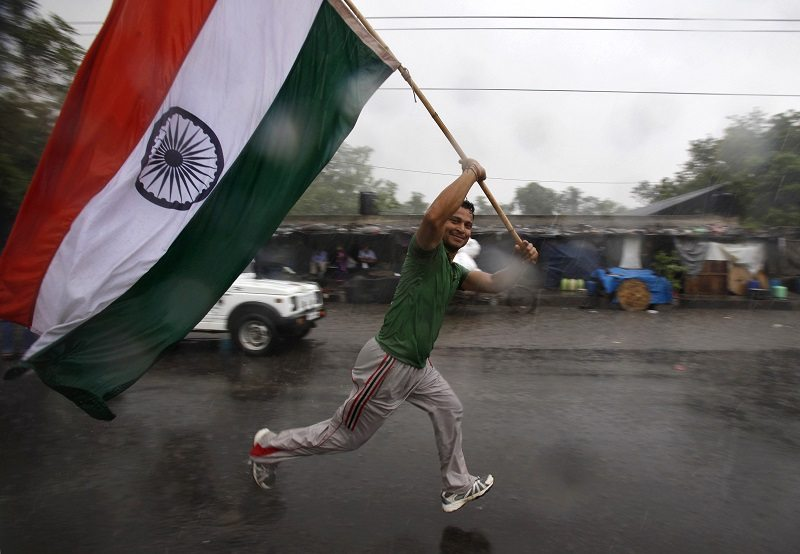 A supporter waves the Indian national flag as he runs in front of a vehicle carrying veteran Indian social activist Anna Hazare after he leaves Tihar jail in New Delhi August 19, 2011. A vast and jubilant crowd cheered as Gandhian activist Hazare walked out of jail in New Delhi on Friday to carry on a hunger strike in public, the latest act in a drama of popular fury over corruption that has put India's government in a bind. REUTERS/Adnan Abidi (INDIA - Tags: POLITICS) - RTR2Q3NZ