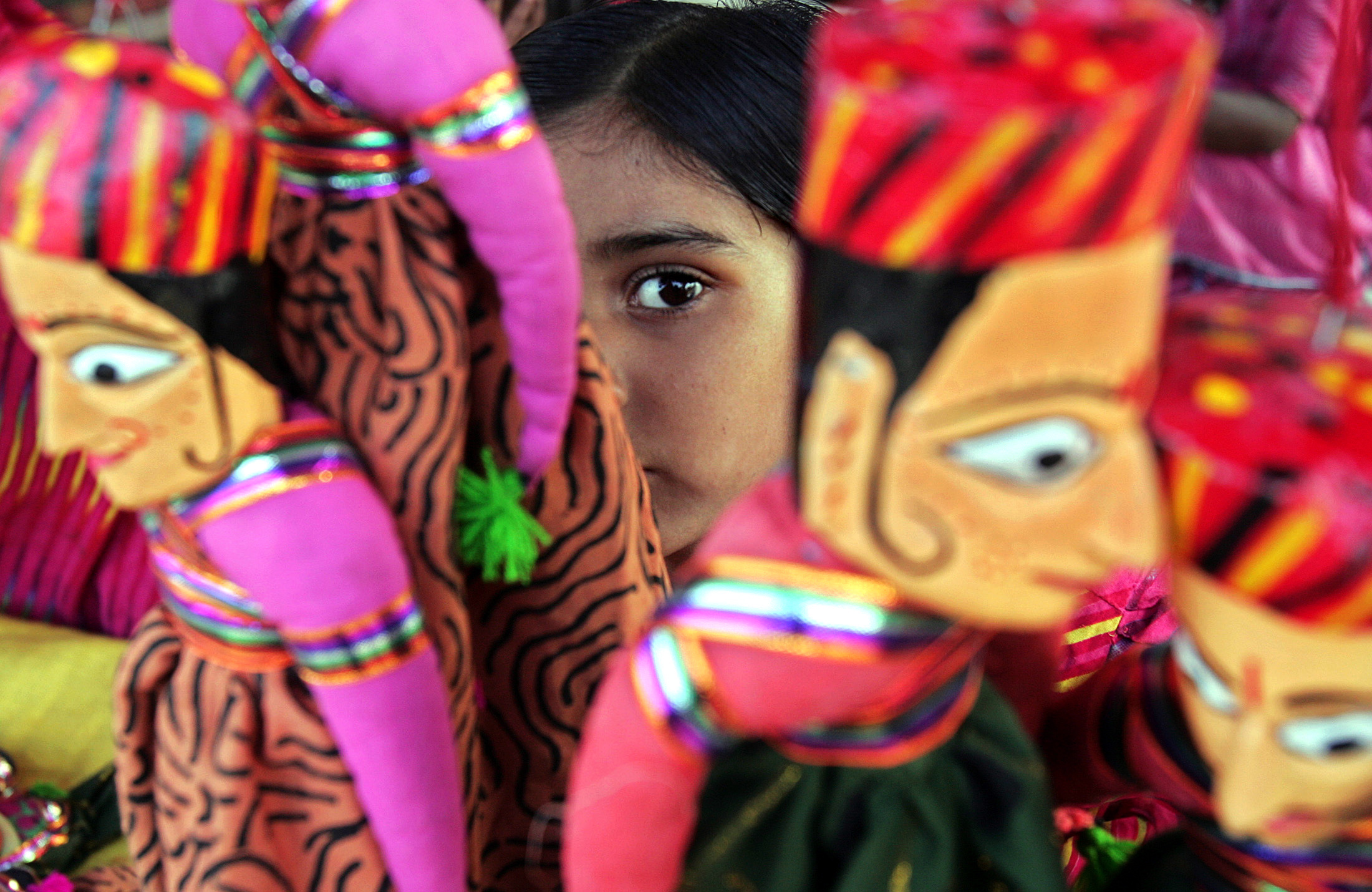An Indian girl from the western Indian state of Gujarat looks through the puppets at a stall during a handicraft fair in the eastern Indian city of Kolkata November 28, 2005. REUTERS/Parth Sanyal - RTR1BQEC