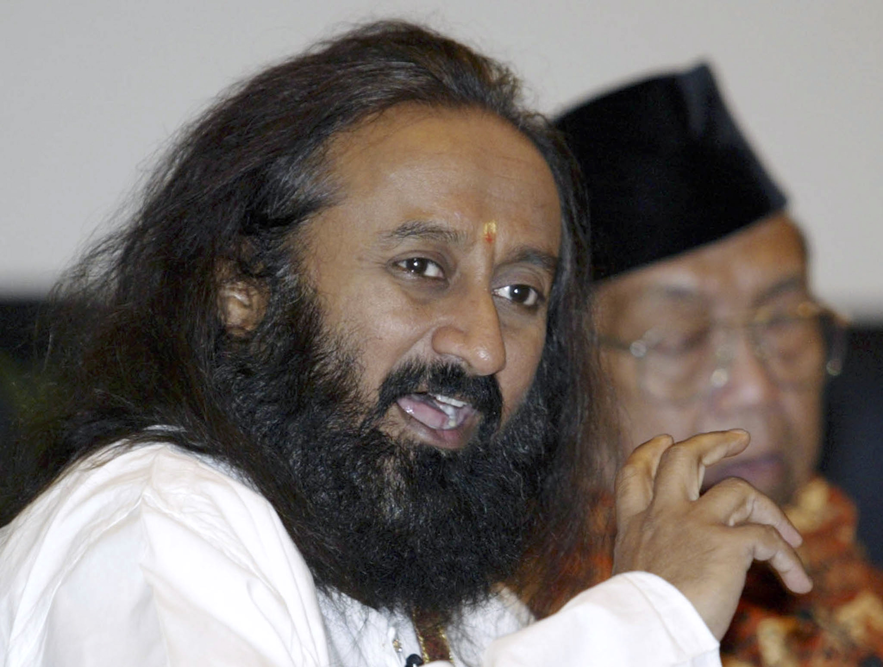 A Hindu leader Sri Sri Ravi Shankar (L) from India speaks next to former Indonesian president Abdurrahman Wahid during a meeting of religious leaders in Jimbaran, Bali, June 12, 2007.The meeting is partly aimed at countering an Iranian-backed conference last year that questioned the existence of the Holocaust. REUTERS/Murdani Usman  (INDONESIA) - RTR1QPSS