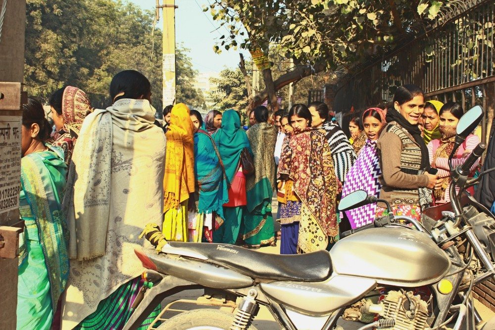Female workers gather at one point, some waiting for the rides to the factories and some waiting to be selected by the factory contractors.