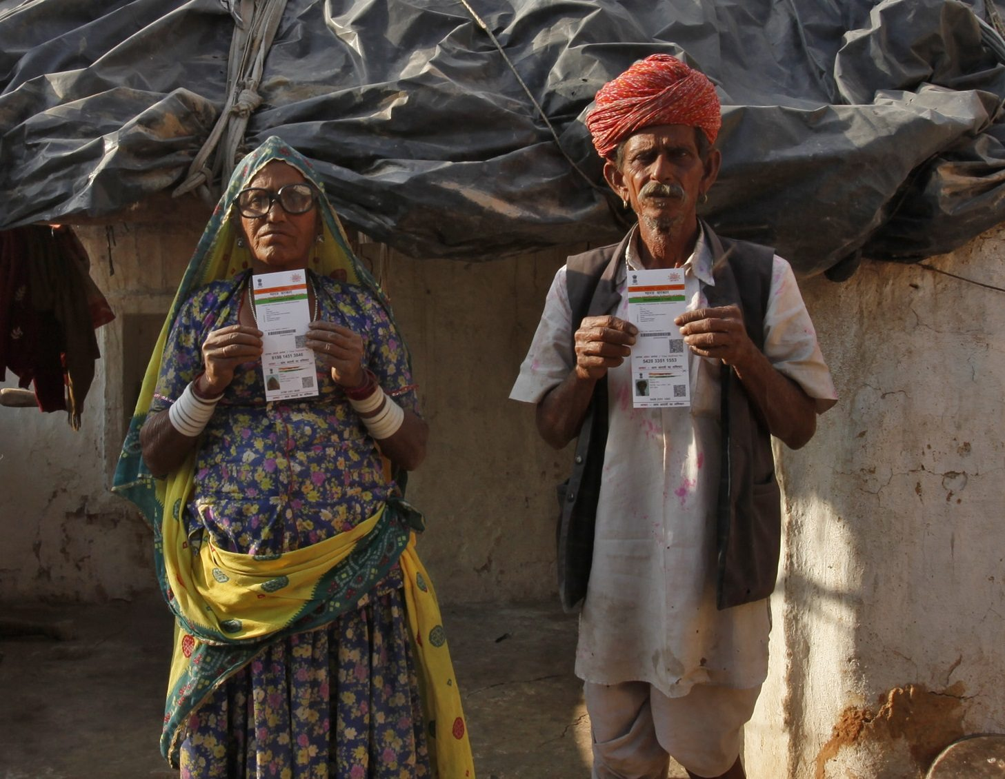 Ghewar Ram (R), 55, and his wife Champa Devi, 54, display their Unique Identification (UID) cards outside their hut at Merta district in the desert Indian state of Rajasthan February 21, 2013. In a more ambitious version of programmes that have slashed poverty in Brazil and Mexico, the Indian government has begun to use the UID database, known as Aadhaar, to make direct cash transfers to the poor, in an attempt to cut out frauds who siphon billions of dollars from welfare schemes. Picture taken February 21, 2013. REUTERS/Mansi Thapliyal (INDIA - Tags: SOCIETY POVERTY SCIENCE TECHNOLOGY BUSINESS TPX IMAGES OF THE DAY) - RTR3EDRN