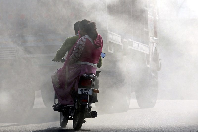 "A woman on a motorcycle covers her face from smoke coming from burning garbage dump in Jammu December 7, 2009. The biggest climate meeting in history, with 15,000 participants from 192 nations, opened in Copenhagen on Monday with hosts Denmark saying an unmissable opportunity to protect the planet was ""within reach"". REUTERS/Mukesh Gupta (INDIAN-ADMINISTERED KASHMIR ENVIRONMENT SOCIETY TRANSPORT) - RTXRKSW"