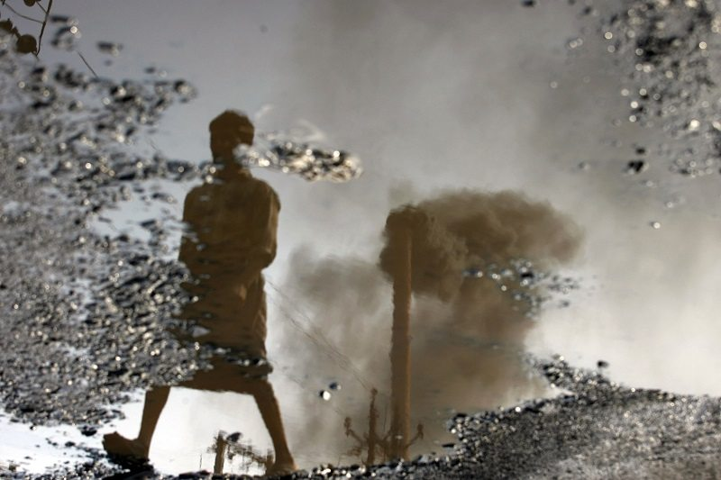 A chimney is reflected in a puddle polluted with chemicals at an industrial area of the western Indian city of Surat November 25, 2009. Just next to India's west coast, Surat is learning to live with big upheavals and now wants to become a front-runner in preparing for the impact of climate change in a country with fast-rising emissions but generally low environmental awareness. The picture was rotated 180 degrees. Picture taken November 25, 2009. To match feature INDIA-CLIMATE/ADAPTATION REUTERS/Arko Datta/Files (INDIA ENVIRONMENT POLITICS BUSINESS) - RTXRLAS