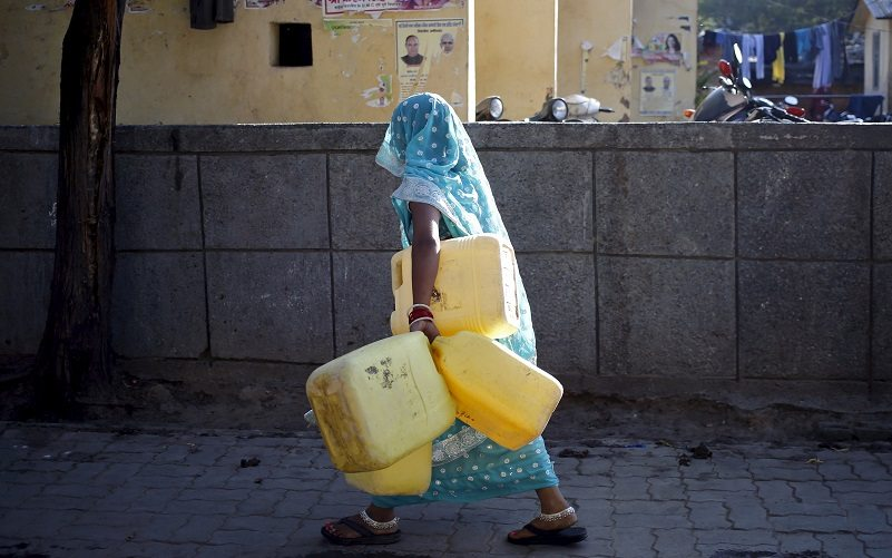 A woman carries empty containers to fetch water from a municipal water tap in New Delhi, India, February 21, 2016. India deployed thousands of troops in a northern state on Sunday to quell protests that have severely hit water supplies to Delhi, a city of more than 20 million people, forced factories to close and killed 10 people. Rioting and looting in Haryana by the Jats, a rural caste, is symptomatic of increasingly fierce competition for government jobs and educational openings in India, whose growing population is set to overtake China's within a decade. REUTERS/Anindito Mukherjee - RTX27W7D
