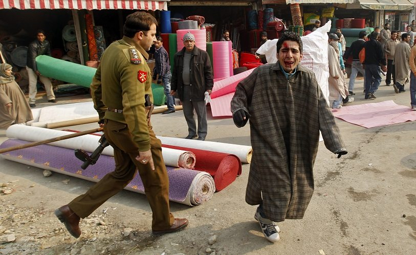 An Indian police officer walks past an injured youth after police chased away Kashmiri Shi'ite mourners who tried to defy a curfew and take out a Muharram procession, in Srinagar December 15, 2010. Authorities on Wednesday imposed a curfew in parts of Srinagar, the summer capital of Indian-administered Kashmir to thwart planned Muharram processions, local media reported. Muslims all over the world mourn the slaying of Imam Hussein, grandson of Prophet Mohammad, during the first ten days of the Islamic month of Muharram. Imam Hussein was killed by his political rivals along with 72 companions in the 7th century battle of Kerbala. The injured boy said that he was beaten by Indian police after he took refuge inside a shop. REUTERS/Fayaz Kabli (INDIAN-ADMINISTERED KASHMIR - Tags: CIVIL UNREST POLITICS RELIGION CRIME LAW) - RTXVQLW