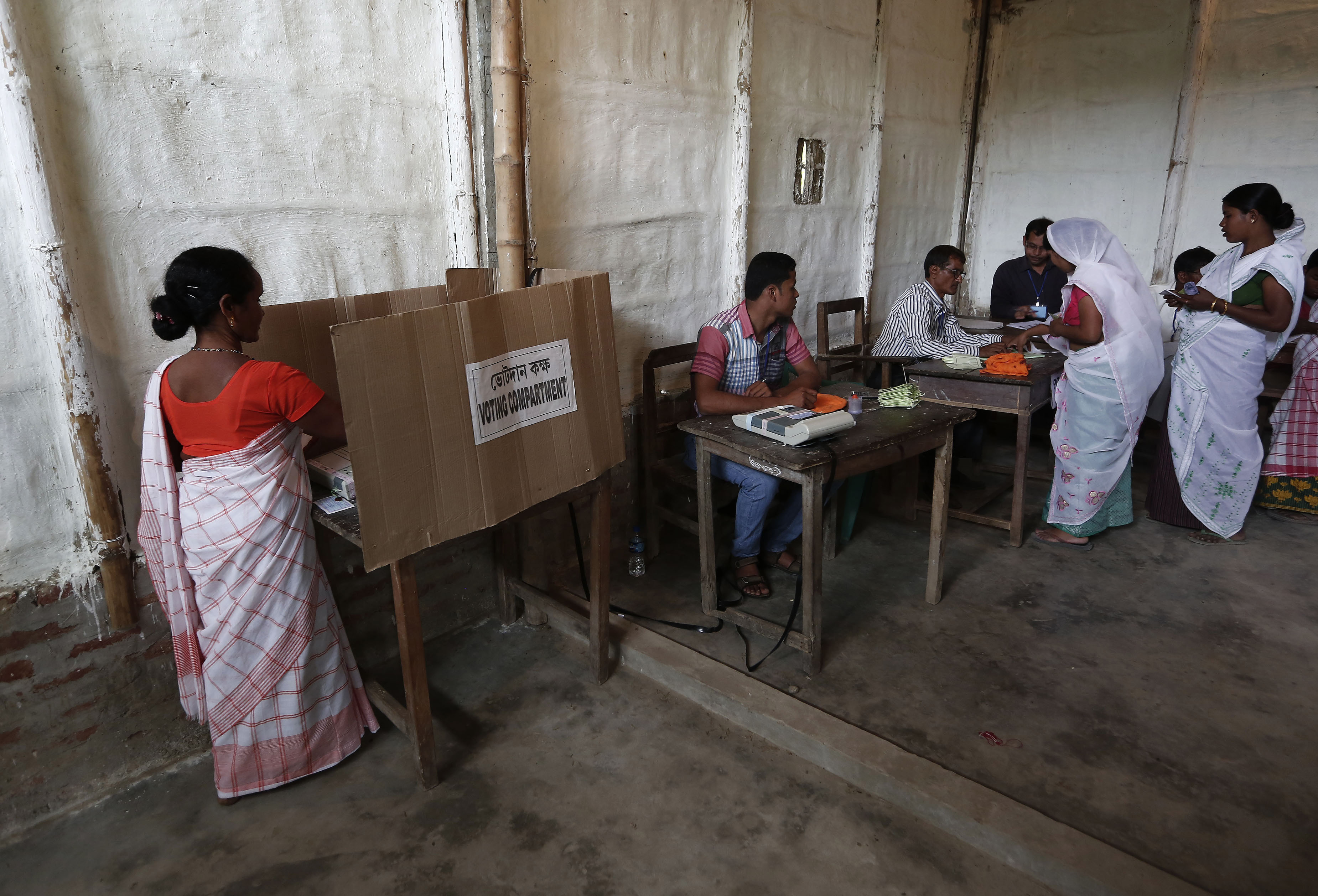 A woman (L) casts her vote with an electronic voting machine as others get their voting slip from an officer at a polling station in Majuli, a large river island in the Brahmaputra river, Jorhat district, in the northeastern Indian state of Assam April 7, 2014. The first electors cast their votes in the world's biggest election on Monday with Hindu nationalist opposition candidate Narendra Modi seen holding a strong lead on promises of economic revival and jobs but likely to fall short of a majority. REUTERS/Adnan Abidi (INDIA - Tags: POLITICS ELECTIONS) - RTR3K8J6