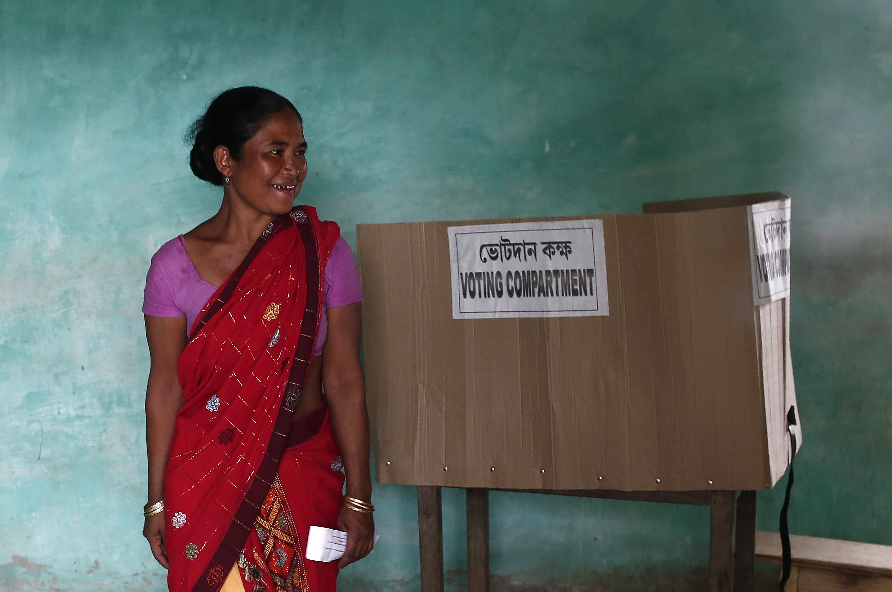 A woman smiles after casting her vote at a polling station in Majuli, a large river island in the Brahmaputra river, Jorhat district, in the northeastern Indian state of Assam April 7, 2014. The first electors cast their votes in the world's biggest election on Monday with Hindu nationalist opposition candidate Narendra Modi seen holding a strong lead on promises of economic revival and jobs but likely to fall short of a majority. REUTERS/Adnan Abidi (INDIA - Tags: POLITICS ELECTIONS) - RTR3KA4Y