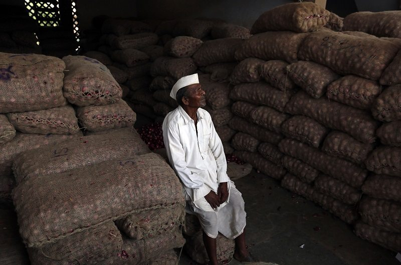 A farmer sits amid stacked sacks of onions as he waits for customers at a wholesale onion and potato market in the western Indian city of Ahmedabad November 14, 2014. India's inflation dropped to a new multi-year low in October, helped by slower annual rises in food and fuel prices, intensifying pressure on the central bank to cut interest rates to encourage spending and investment needed to boost growth. REUTERS/Amit Dave (INDIA - Tags: FOOD BUSINESS) - RTR4E4MS