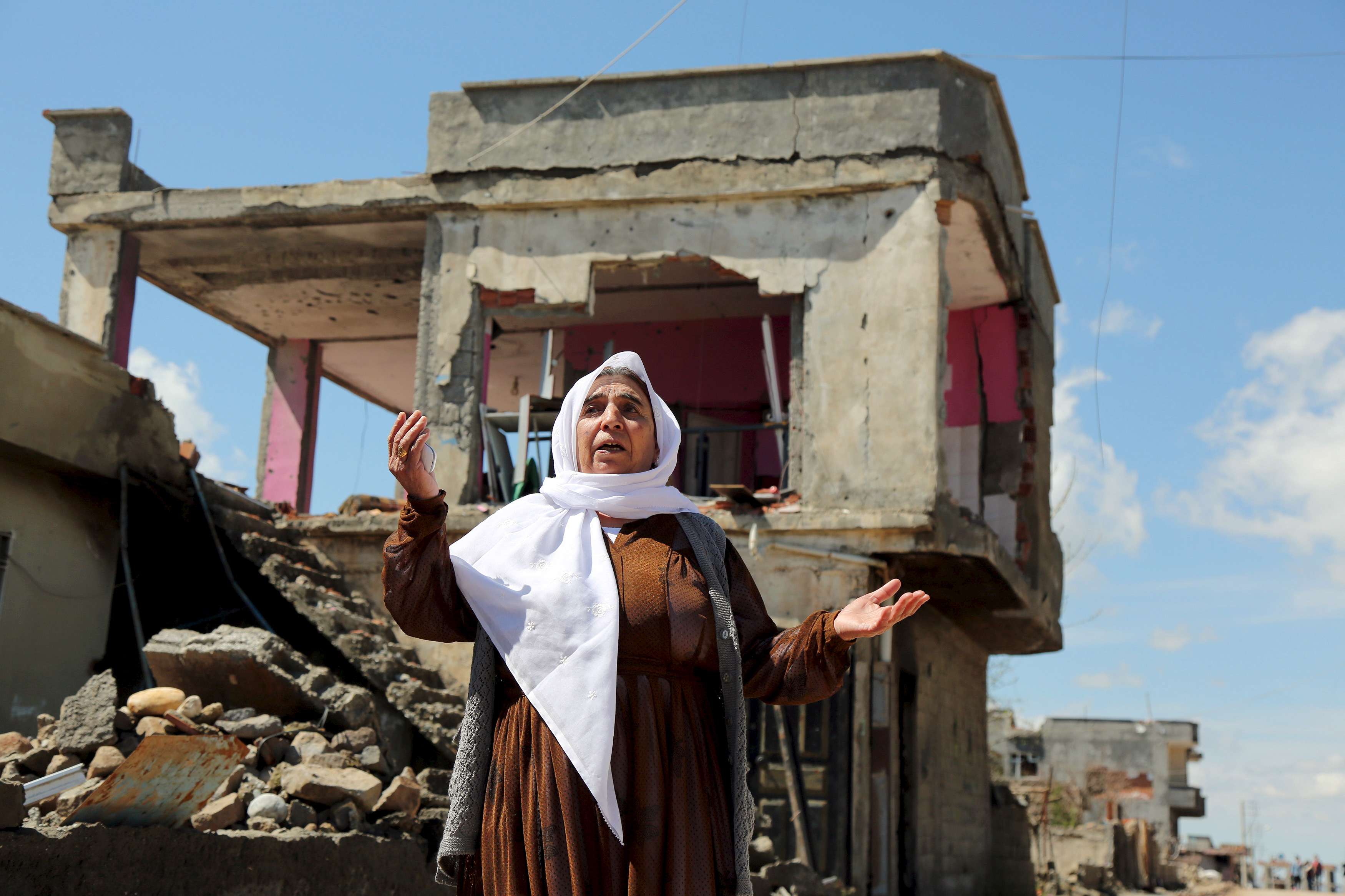A woman reacts as she stands in front of her house, which was damaged during the security operations and clashes between Turkish security forces and Kurdish militants, in the southeastern town of Idil, Turkey, March 31, 2016. REUTERS/Sertac Kayar - RTSCZOS