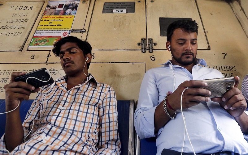 Commuters watch videos on their mobile phones as they travel in a suburban train in Mumbai, India, April 2, 2016. With smartphone sales booming and India preparing for nationwide 4G Internet access, India's film and TV industry hopes the ease of tapping your phone for the latest release will generate profits at last, overcoming the problems of woefully few cinemas and rampant piracy. Picture taken April 2, 2016. REUTERS/Shailesh Andrade - RTSDS09