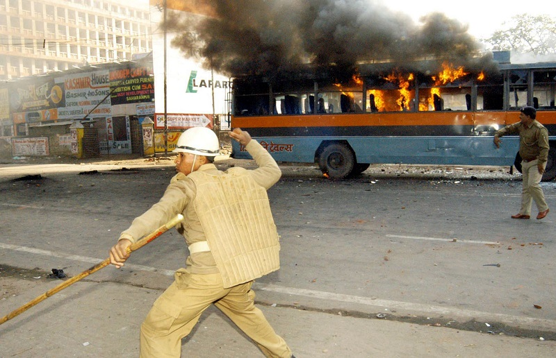 Indian riot police throw stones at demonstrators as a bus burns during a general strike in the city of Patna, state capital of the eastern state of Bihar January 3, 2003. More than 500 people in eastern India were arrested on Friday as mobs torched government buildings and clashed with security forces during a general strike to protest the police killing of three youths. REUTERS/Krishna Murari Kishan JSG/CP - RTRG22S