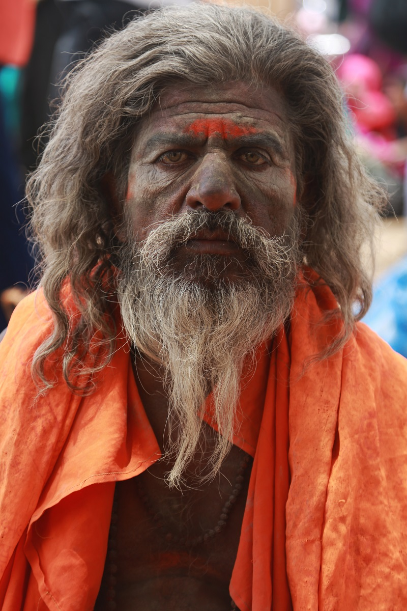 A sadhu focuses his strong gaze directly at the camera.