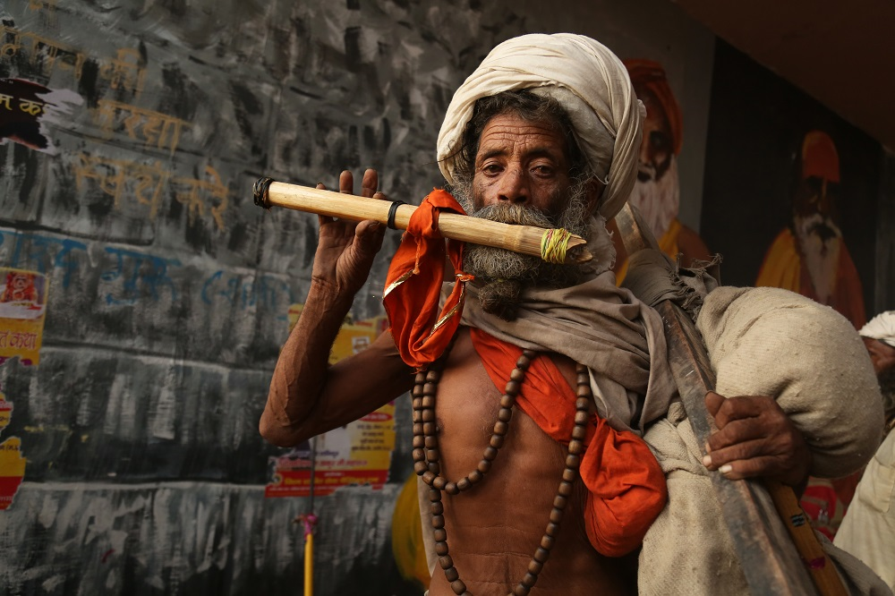 A sadhu walking with his belongings on one shoulder plays a flute with his other hand.