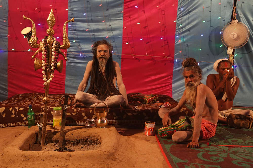 Naga sadhus seated inside a tent. A man on the side smokes a chillum.