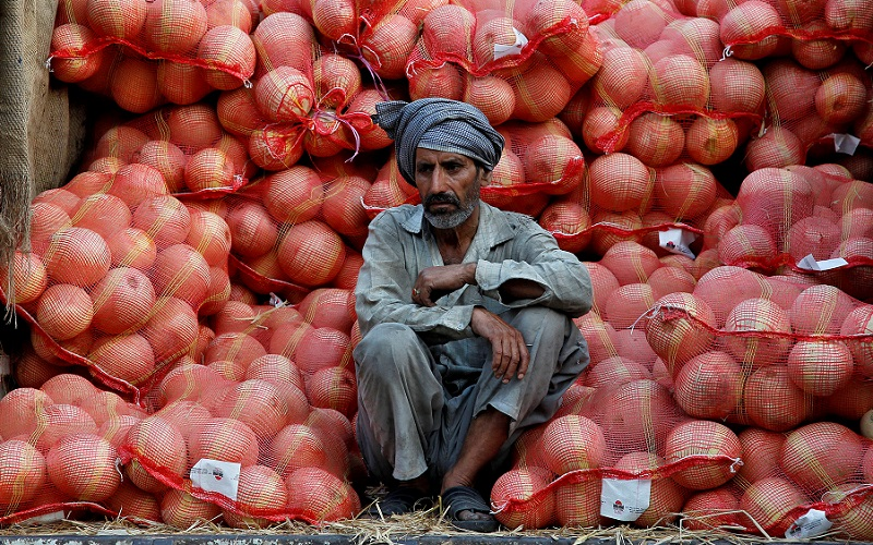A farmer sits on a trolley loaded with melons