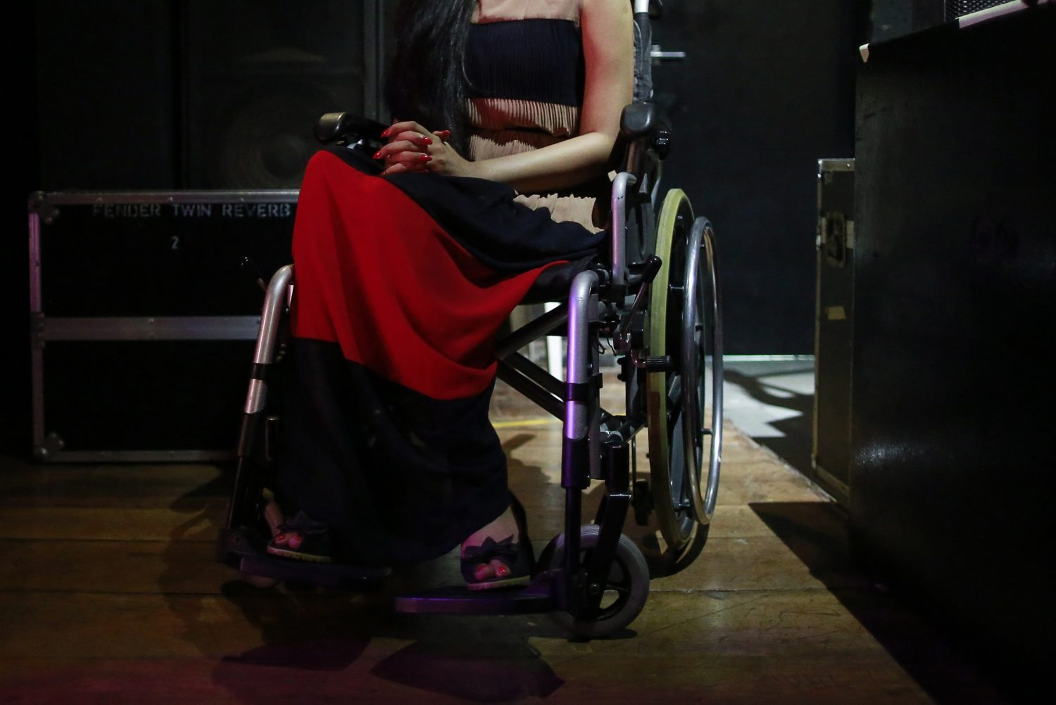 A competitor watches a performance from backstage during the Miss Wheelchair India beauty pageant in Mumbai November 26, 2014. Seven women from across India participated in the country's second wheelchair beauty pageant, which aims to open doors for the wheelchair-bound in modelling, film and television, according to organisers. REUTERS/Danish Siddiqui (INDIA - Tags: SOCIETY) - RTR4FQ6S