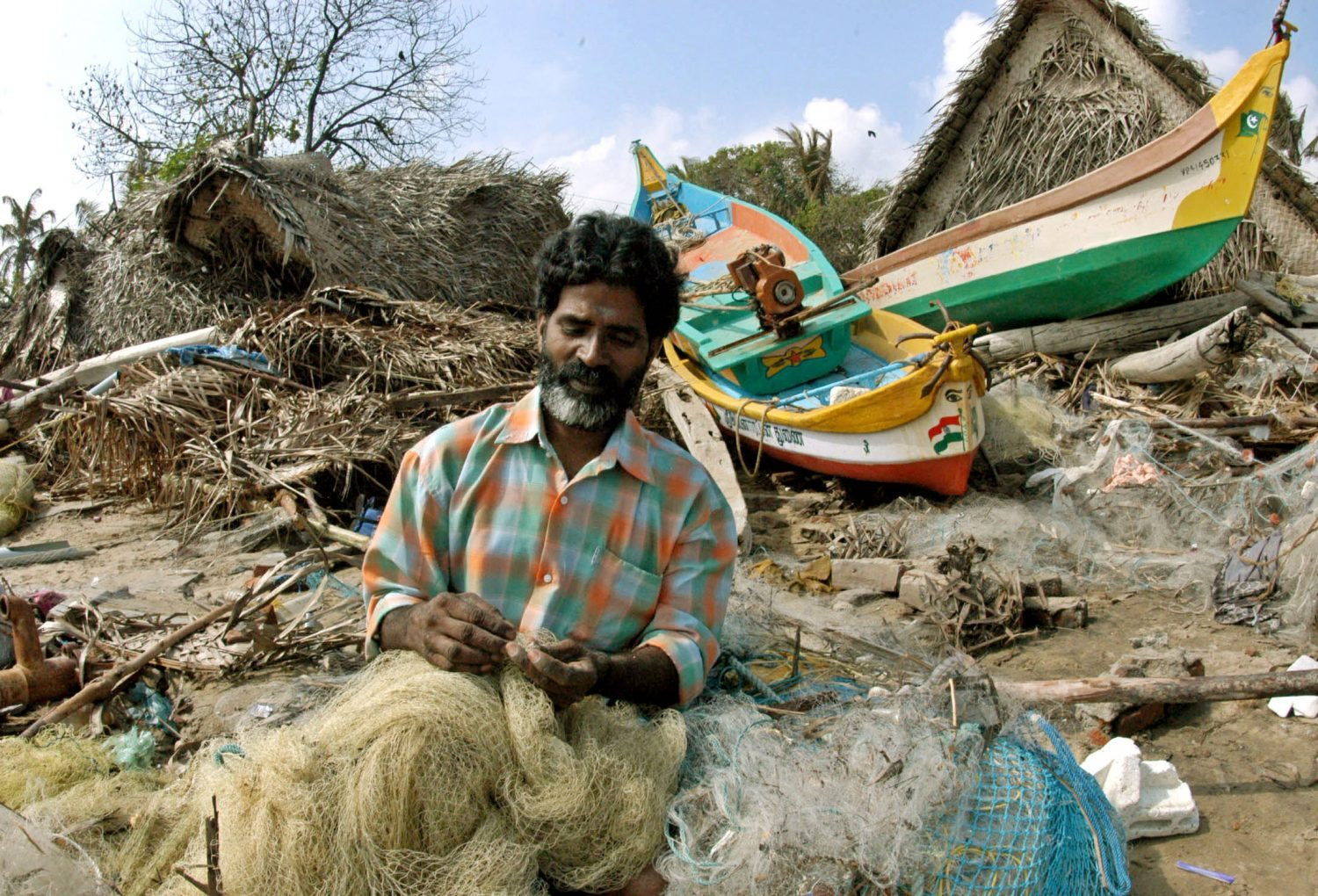 An Indian fisherman sews his fishing net outside his damaged hut after a tsunami hit the southern Indian city of Madras December 27, 2004. Soldiers searched for bodies in treetops, families wept over the dead laid on beaches and rescuers scoured coral isles for missing tourists as Asia counted the cost on Monday of a tidal wave triggered by an earthquake that killed thousands. - RTXN4CU