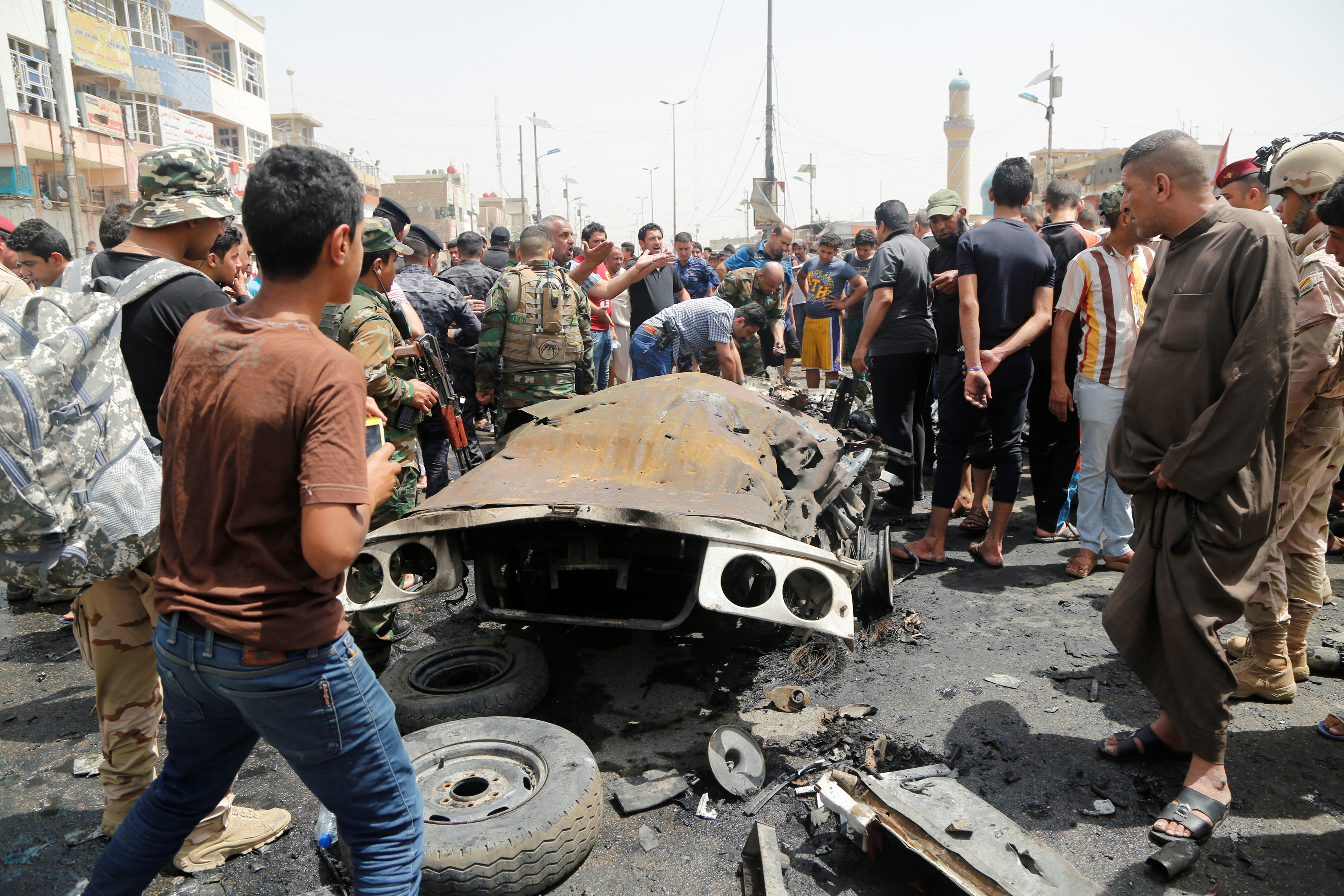 People gather at the scene of a car bomb attack in Baghdad's mainly Shi'ite district of Sadr City, Iraq, May 11, 2016. REUTERS/Wissm al-Okili - RTX2DRWQ