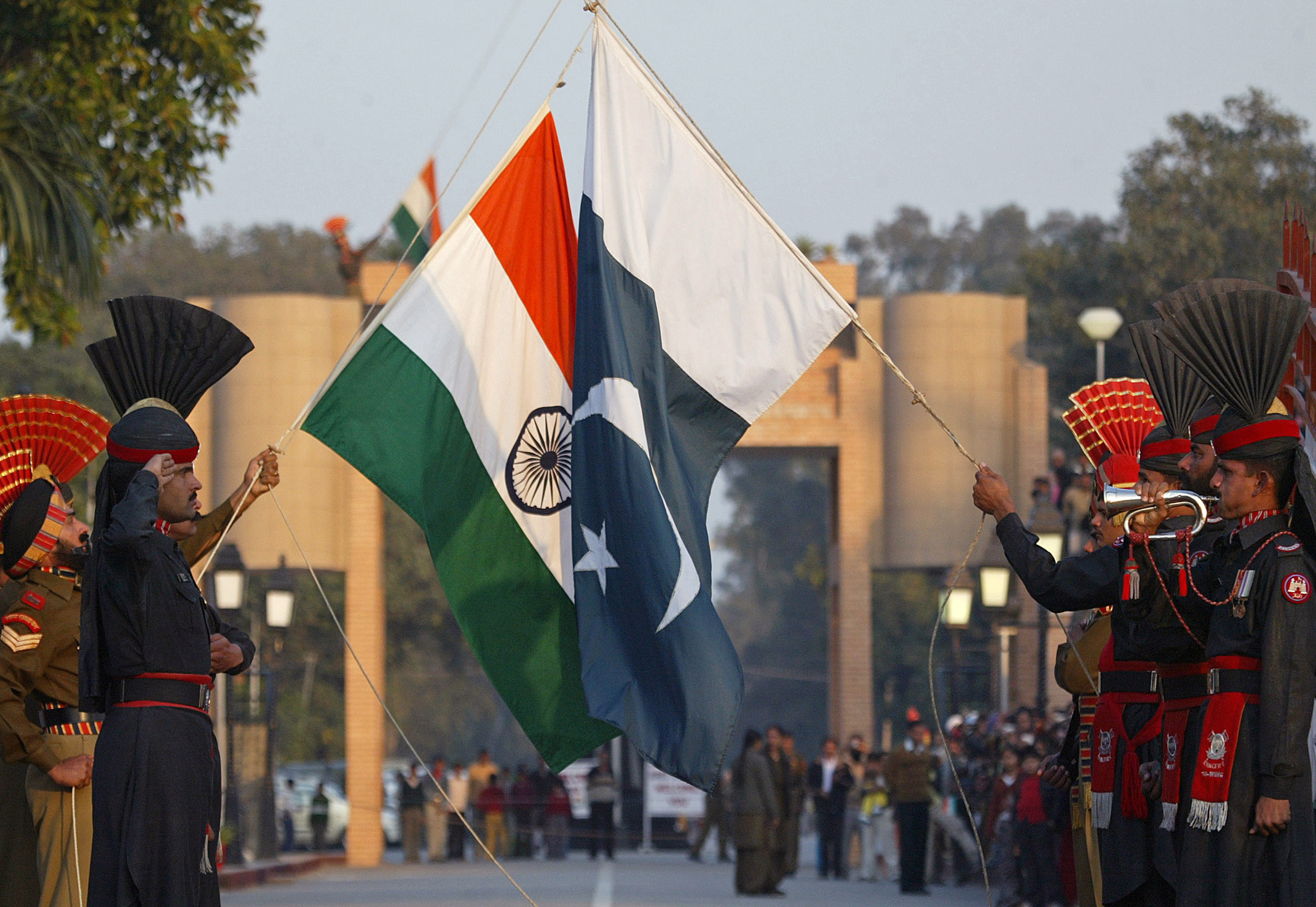 Pakistan Rangers and Indian Border Security Force personnel take part in the daily flag lowering ceremony at their joint border post of Wagah near Lahore January 10 , 2007. On Saturday, Indian Foreign Minister Pranab Mukherjee is due in Islamabad for another round of talks in a peace process that has yet to yield substantial results, but it has at least ushered in a no-war phase in relations. REUTERS/Mohsin Raza (PAKISTAN) - RTR1L45Z