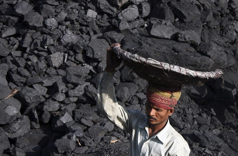 A labourer carries coal in a basket to load it in a truck at a coal store in the northern Indian city of Chandigarh October 25, 2010. Demand for coal is forecast to grow 11 percent a year in India, which aims to halve its peak-hour power deficit of nearly 14 percent over the next two years and triple its generation capacity over the next decade. REUTERS/Ajay Verma (INDIA - Tags: BUSINESS ENERGY) - RTXTTFB