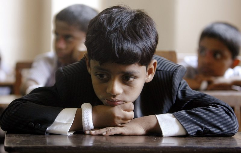 """Azharuddin Ismail, who acted as young Salim in the Oscar-winning movie """"Slumdog Millionaire"""", sits with his friends in a classroom before attending their school's cultural day in Mumbai February 28, 2009. Ismail returned to Mumbai on Thursday after attending the 81st Academy Awards in Los Angeles. REUTERS/Punit Paranjpe (INDIA) - RTXC6VT"""