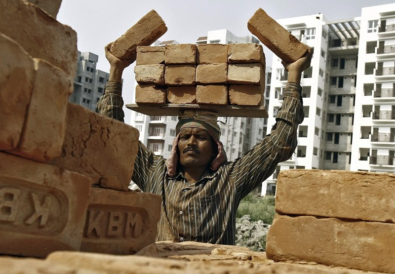 A labourer stacks bricks on his head at the construction site of a residential complex in Kolkata February 28, 2015. India's Finance Minister Arun Jaitley on Saturday announced a budget aimed at high growth, saying the pace of cutting the fiscal deficit would slow as he seeks to boost investment and ensure that ordinary people benefit. REUTERS/Rupak De Chowdhuri (INDIA - Tags: BUSINESS CONSTRUCTION EMPLOYMENT) - RTR4RIJ7