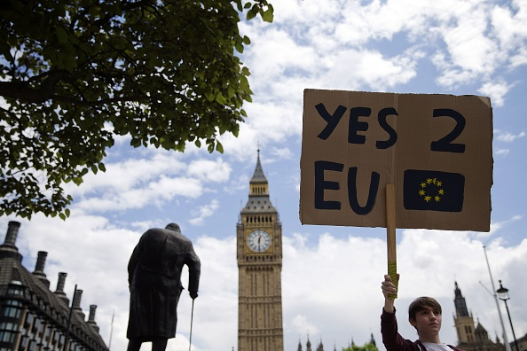 TOPSHOT - A demonstrator holds a placard during a protest against the outcome of the UK's June 23 referendum on the European Union (EU), in central London on June 25, 2016. The result of Britain's June 23 referendum vote to leave the European Union (EU) has pitted parents against children, cities against rural areas, north against south and university graduates against those with fewer qualifications. London, Scotland and Northern Ireland voted to remain in the EU but Wales and large swathes of England, particularly former industrial hubs in the north with many disaffected workers, backed a Brexit. / AFP / JUSTIN TALLIS        (Photo credit should read JUSTIN TALLIS/AFP/Getty Images)