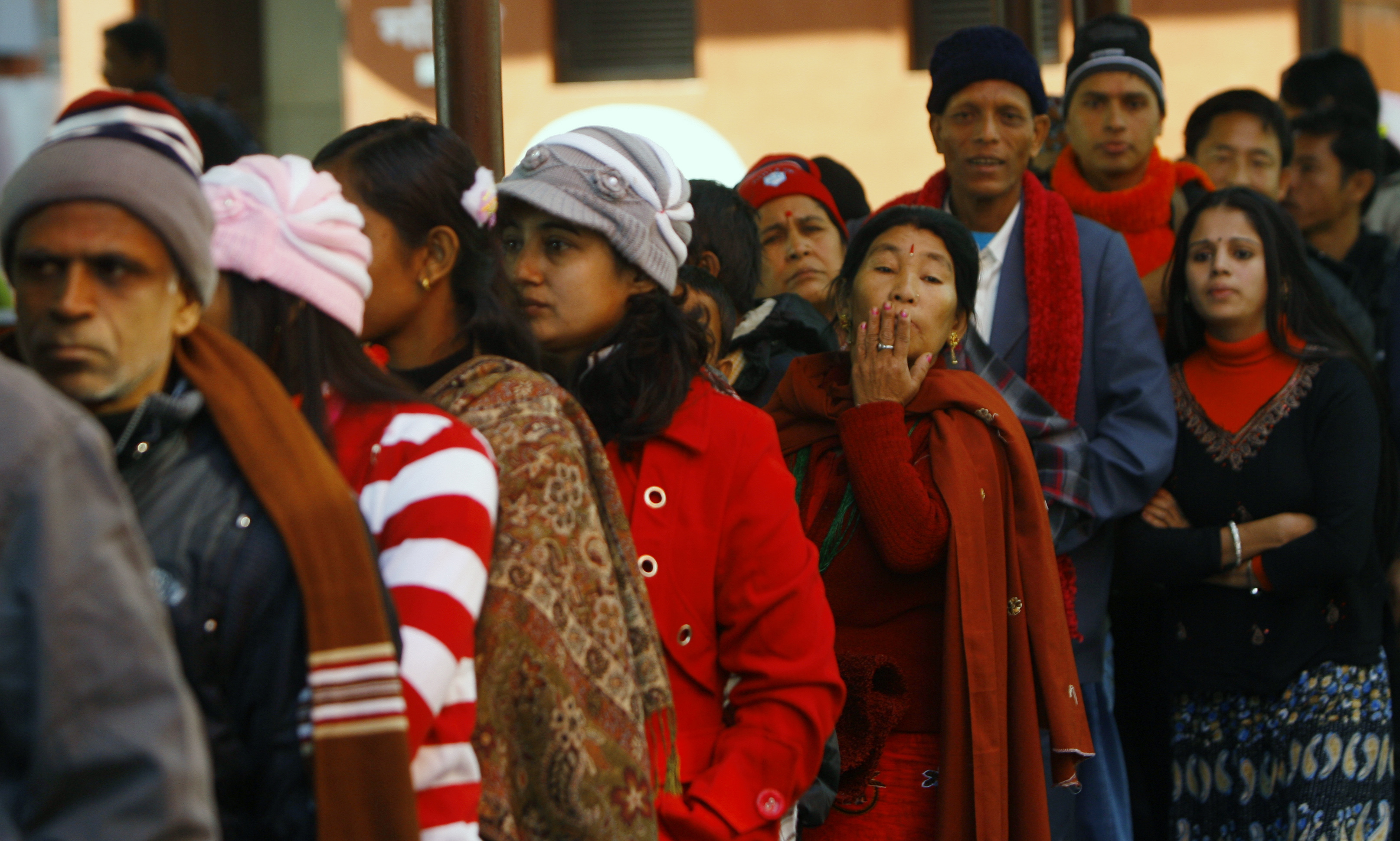 Bhutanese refugees wait for food at a ca