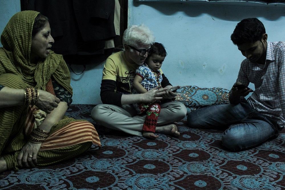 """My parents are first cousins. Albinism being a recessive trait, gets magnified if the parents are closely related. Even my 'Nani' was an albino."" Faizan at home with his one-year-old niece as his mother and friend Subhan look on."