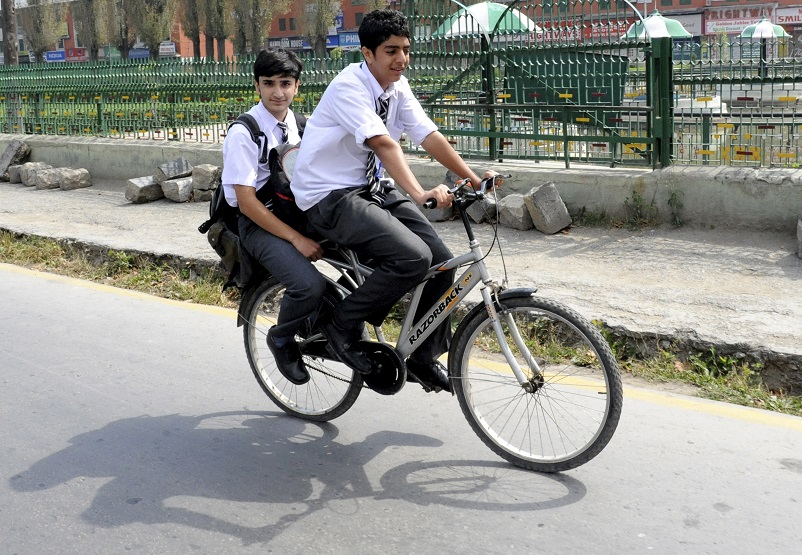 "School children cycle along a road to their school during a curfew in Srinagar on September 27, 2010. Authorities had asked both the state and private-owned schools to reopen despite a curfew and a general strike called by separatists. Some schools in Indian Kashmir have re-opened after remaining shut for most of the time during months of violent pro-independence protests and strict curfews but attendance was thin. In Srinagar's main government school, Sri Pratap School, only 50 students had braved curfew to reach the school.""This is not education. This is how the government wants us to punish for taking part in pro-freedom demonstrations,"" said Yasir Misger, an 11th standard student, who was told by the teachers to make it to school ""come what may."". AFP PHOTO/Rouf BHAT (Photo credit should read ROUF BHAT/AFP/Getty Images)"