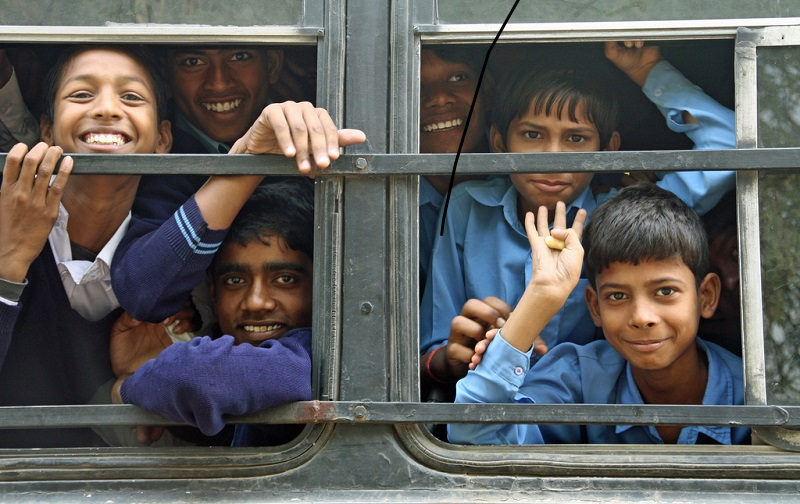 young boys looking out of the window of their school bus