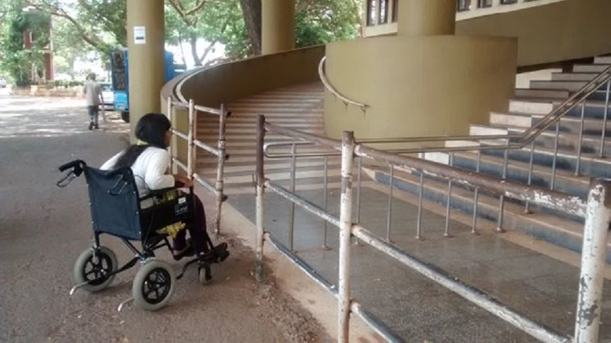 A person in a wheel chair in front of a ramp that is at a higher level than the ground, making it inaccessible.