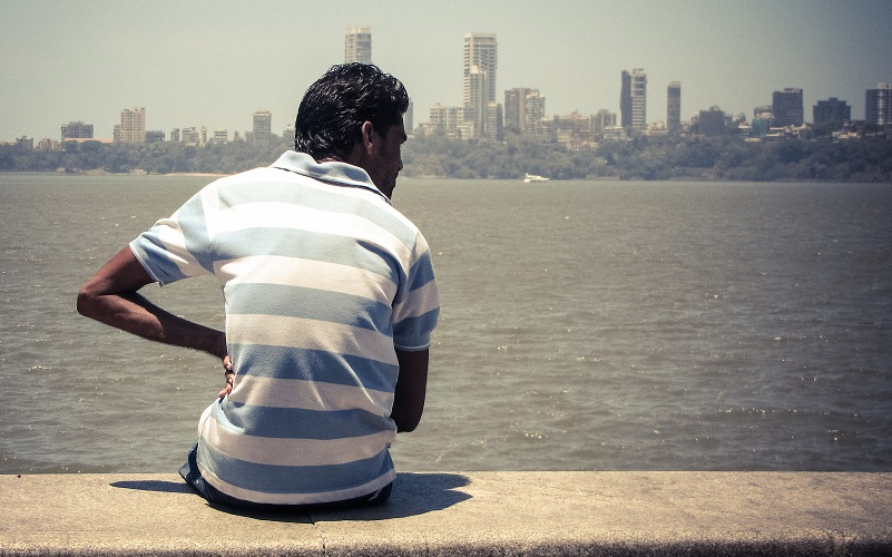 Man sitting on a parapet by the sea. Mumbai shoreline available in the distance