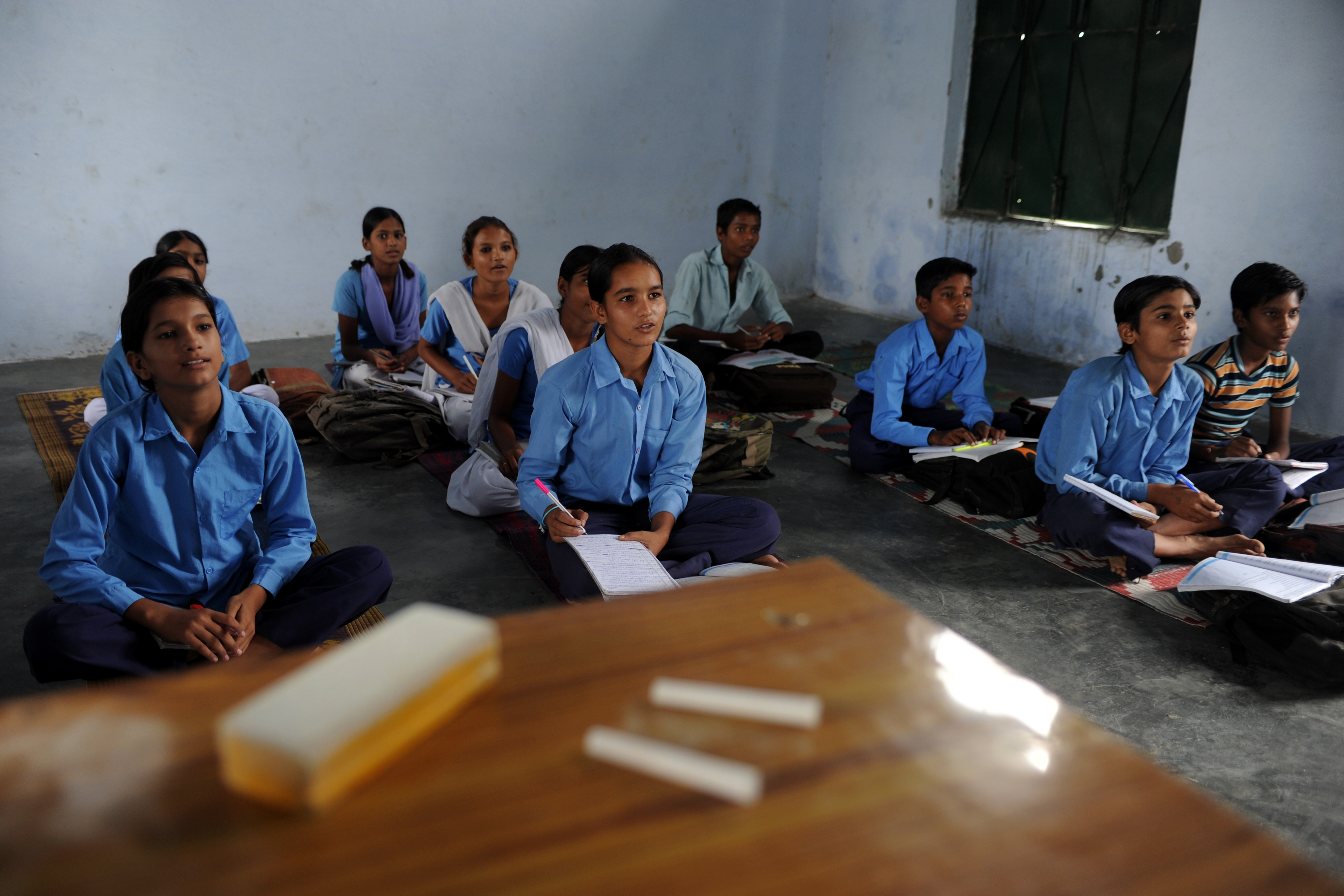TO GO WITH Lifestyle-Asia-education-India,FEATURE by Adam Plowright Indian schoolchildren read in a classroom at a government school in Bagpath district in Uttar Pradesh on August 30, 2012. On any given day in a state primary school in India, up to one in four teachers is missing. The cost for a country that sees its young population as its ticket to superpower status is huge. In the poor and agricultural district of Baghpat in Uttar Pradesh, a state home to nearly 200 million people or one in six Indians, absences afflict pupils and fellow teachers alike. AFP PHOTO/SAJJAD HUSSAIN (Photo credit should read SAJJAD HUSSAIN/AFP/GettyImages)