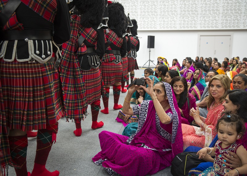 LONDON, ENGLAND - JULY 12: Community members watch the Shree Muktajeeven Swamibapa pipe band perform at Guru Purnima, an Indian festival dedicated to spiritual leaders, at Shree Swaminarayan Mandir, a major new Hindu temple being built in Kingsbury on July 12, 2014 in London, England. The pipe band was established in 1972 in honour of Shree Muktajeeven Swamibapa who, after enjoying a performance by a Scottish pipe band in Trafalgar Square during a visit to London in 1969, inspired his disciples in the United Kingdom to form a pipe band. The original nine members in the band - drum major, four pipers, and four snares - were trained by world-renowned pipe band competition judge Major James Caution. Today the band has around fifty playing members who all live in the North London area and have strong ties to India. The band's repertoire comprises both traditionally Scottish pipe music and Indian melodies, bhajans, and original compositions and transpositions of Hindi film songs by band members. The Swaminarayan faith, a branch of Hinduism, was established by Lord Shree Swaminarayan, at the end of the 18th century in Northern India. For much of the 20th Century the faith was led by Jeevanpran Shree Muktajeevan Swamibapa who toured all over India as well as establishing Swaminarayan Temples in East Africa the United Kingdom and the United State of America. The Shree Swaminarayan temple (Mandir) Kingsbury, in the London borough of Brent, is the principal place of worship in the south of England. The Mandir complex, set to fully open at a festival in August, has cost ?20 million to build, all of the money being raised by the community and through the sale of its previous site in Golders Green, which is being developed for housing. (Photo by Rob Stothard/Getty Images)