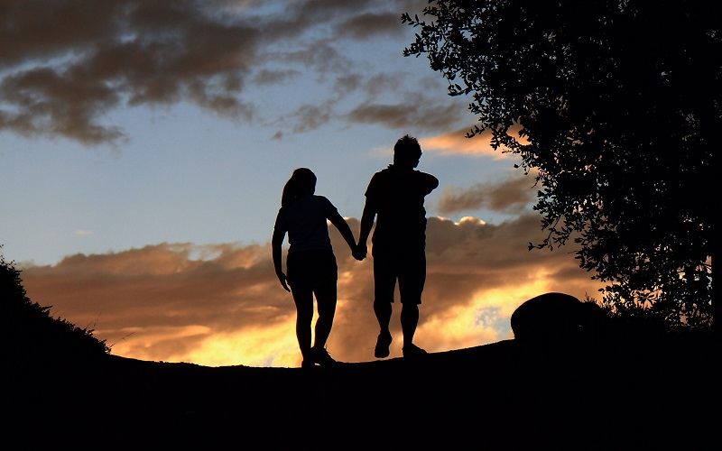 couple walking at sunset.