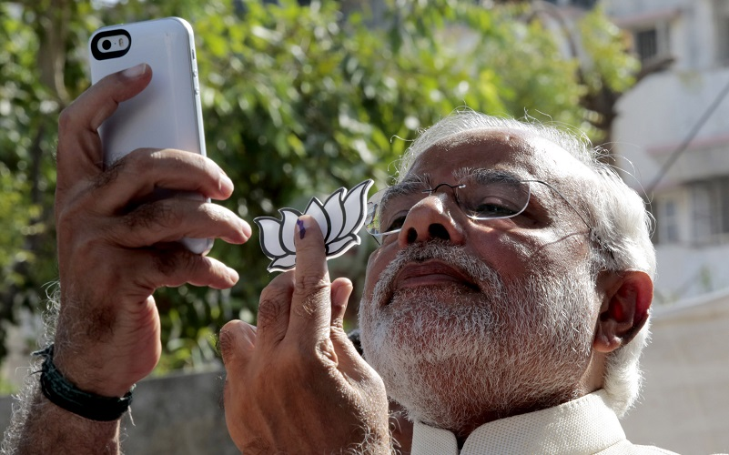 AHMEDABAD, INDIA - APRIL 30: Narendra Modi, prime ministerial candidate of Indias main opposition Bharatiya Janata Party (BJP) takes a selfie after he cast his vote at the seventh phase of the Indian Election in the Indian state of Gujarat, Ahmedabad, India on April 30, 2014. (Photo by Metin Aktas/Anadolu Agency/Getty Images)