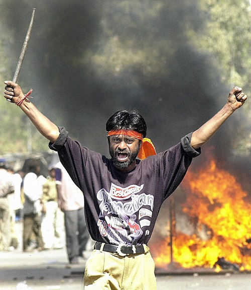 AHMEDABAD, INDIA: (FILES) This picture taken 28 February 2002 shows a Bajranj Dal activist armed with a iron stick shouting slogans against muslims as they went burning muslim shops and attacked residences at Sahapur in Ahmedabad, in revenge for the 27 February 2002 attack by a Muslim mob on a train carrying Hindu activists that left 58 people dead in the Northern state of Gujarat. India's incoming prime minister Manmohan Singh 20 May 2004 criticised the slow prosecution by Gujarat state over the bloody anti-Muslim riots in 2002 and pledged the new government would be firm against religious violence. AFP PHOTO/ SEBASTIAN D'SOUZA (Photo credit should read SEBASTIAN D'SOUZA/AFP/Getty Images)