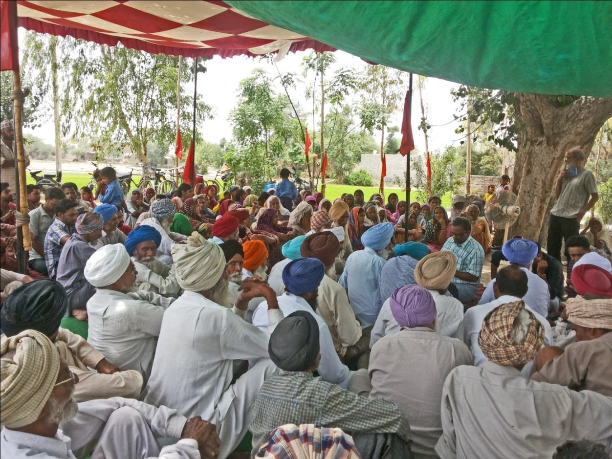 villagers gathered under a makeshift tent