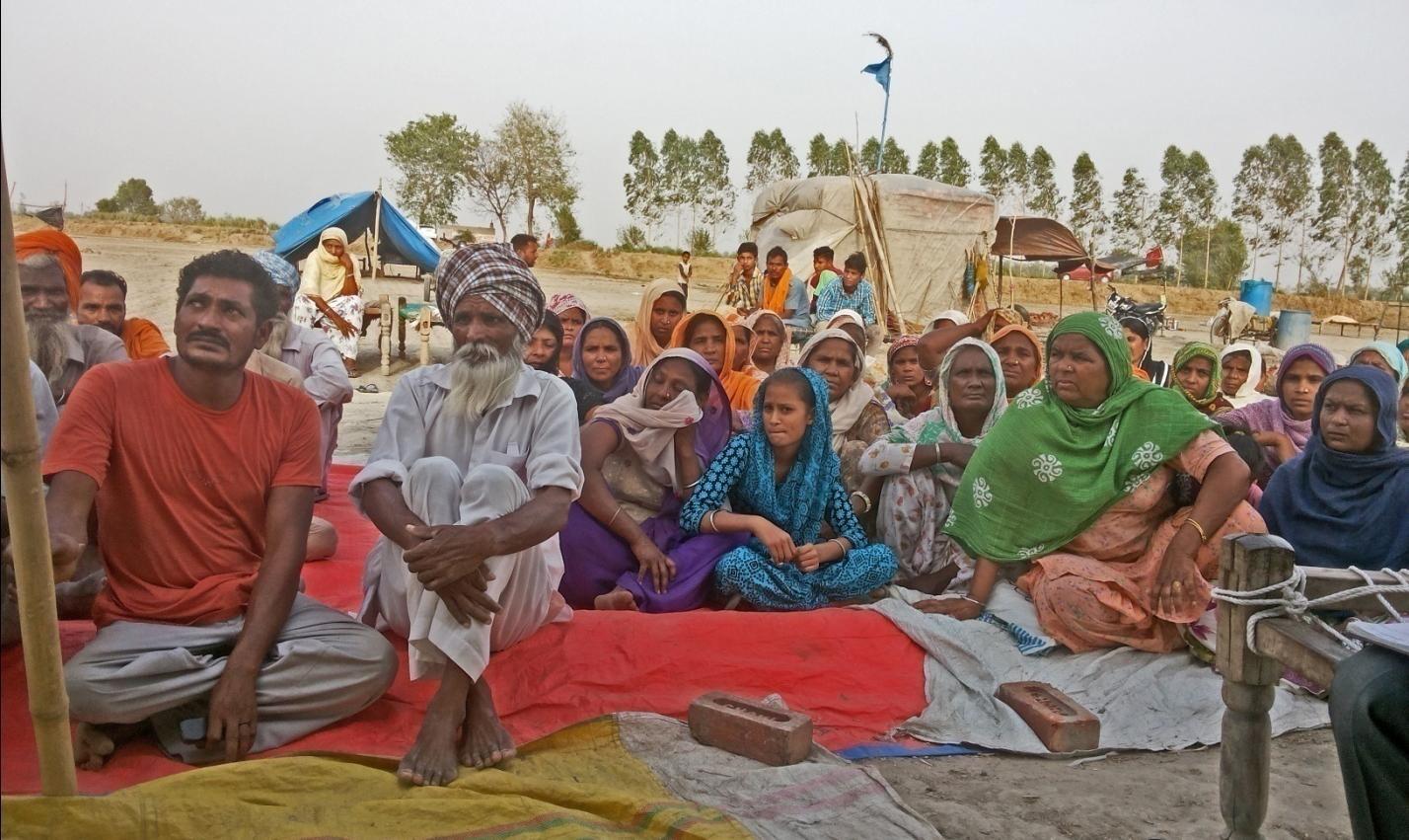 Group of men and women sitting in front of makeshift Gurudwara