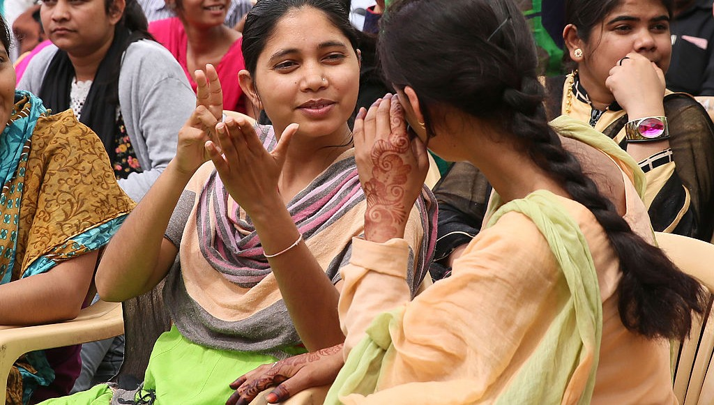 Two girls in a crowd talking to each other using sign language.