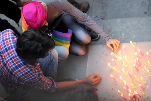 People lighting candles at the pride march
